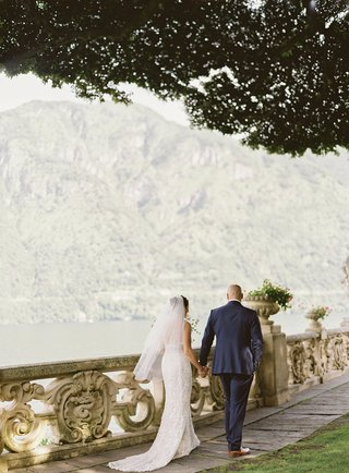 lake-como-wedding-portrait-bride-and-groom-walking-along-railing-by-lake-under-tree