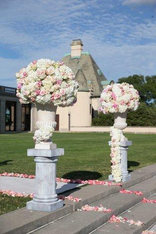 white-hydrangea-pink-rose-flower-arrangement-on-column-riser-aisle-with-pink-flower-petals