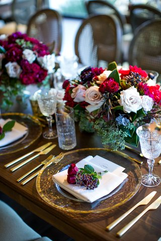 dark-wood-tables-no-linens-low-flower-arrangements-centerpieces-flowers-on-top-of-menu-gold-charger