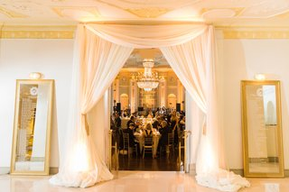 white-canopy-at-reception-entrance-with-seating-charts-in-mirror-gold-frames-on-both-sides