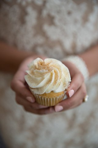 bride-holds-cupckae-with-white-frosting-and-gilded-sugar