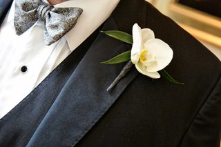 groom-with-white-orchid-boutonniere-on-a-black-suit-jacket-tux-and-gray-detailed-tie