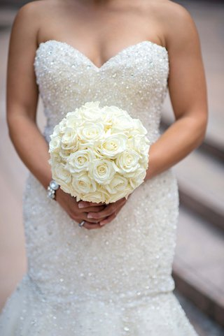 bride-in-beaded-wedding-dress-holding-roses