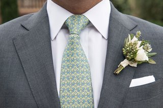 groom-with-patterned-tie-yellow-blue-green-with-natural-bouquet-tied-with-ribbon-greenery-white-rose