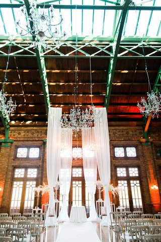wedding-ceremony-in-historic-building-with-tall-drapery-crystal-chandeliers-wood-brick-elements