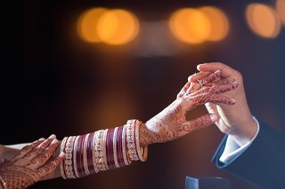 groom-puts-diamond-wedding-ring-on-indian-brides-hand-with-henna-and-bracelets