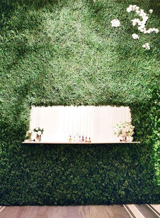 wedding-bar-with-alcohol-displayed-and-flower-arrangements-inside-hedge-wall-at-wedding