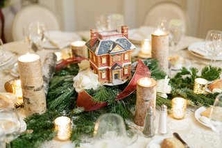 winter-wedding-reception-table-with-dickens-village-series-house-evergreen-white-roses-red