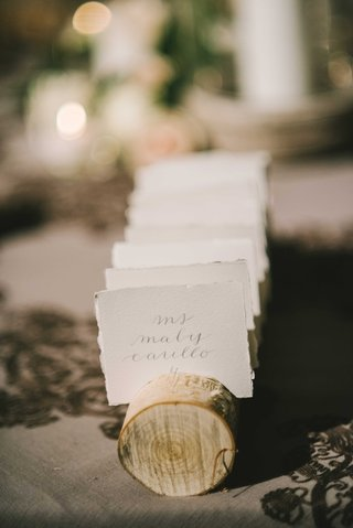 simple-escort-cards-placed-in-notches-of-thick-branches-for-outdoor-inspired-wedding