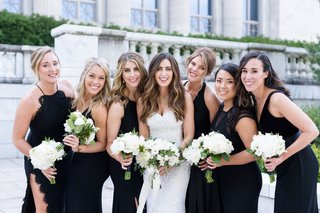 wedding-photo-of-bride-with-bridesmaids-mismatch-black-dresses-white-bouquets-greenery-ribbon