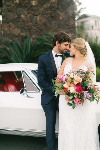 bride-with-pretty-braided-hairstyle-groom-bow-tie-tropical-bouquet-rose-orchid-greenery-classic-car