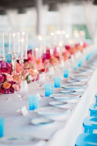 destination-wedding-in-capri-italy-with-bright-pink-flowers-and-bright-blue-glasses-and-chairs
