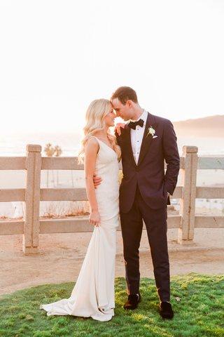 bride-in-v-neck-beaded-wedding-dress-long-blonde-curled-hair-groom-tuxedo-palisades-park-california