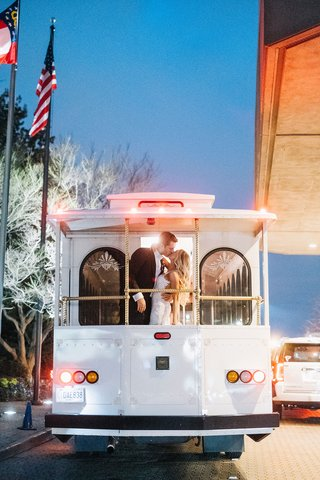 bride-in-berta-wedding-dress-long-blonde-hair-kissing-groom-on-back-of-trolley-car-white-flags