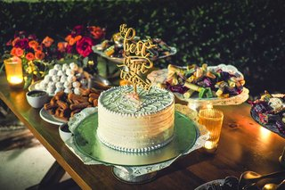 a-small-white-wedding-cake-with-icing-patterns-and-a-topper-that-reads-the-best-is-yet-to-come