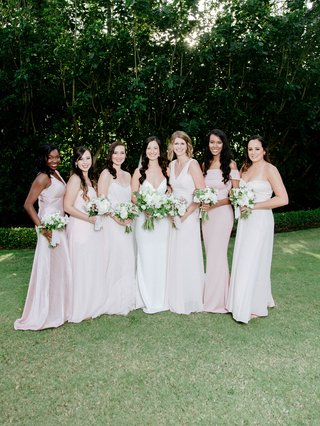 bride-in-crepe-wedding-dress-with-bridesmaids-in-light-pink-dresses-of-their-choosing