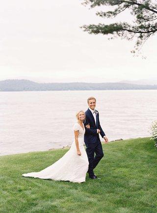 bride-in-carolina-herrera-short-sleeve-lace-wedding-dress-with-groom-in-navy-tuxedo-by-lake-house