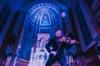 dr-draw-electric-violinist-performing-at-wedding-reception-old-catholic-church-blue-purple-lighting