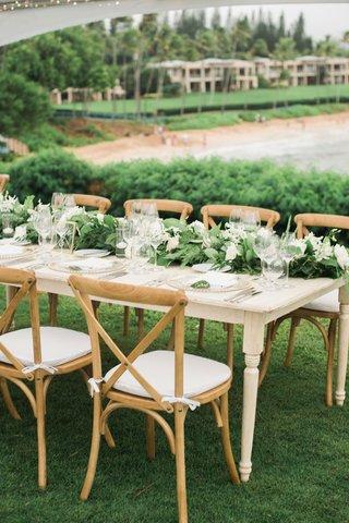 destination-wedding-reception-hawaii-wood-table-chairs-green-garland-centerpiece-beach-view