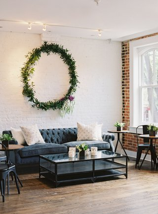 wedding-reception-event-lounge-chesterfield-tufted-sofa-coffee-table-bistro-table-metal-chair-wreath
