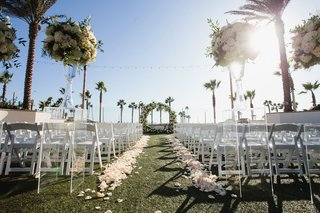 wedding-ceremony-facing-ocean-circle-arch-flowers-by-cina-flower-petals-along-grass-aisle