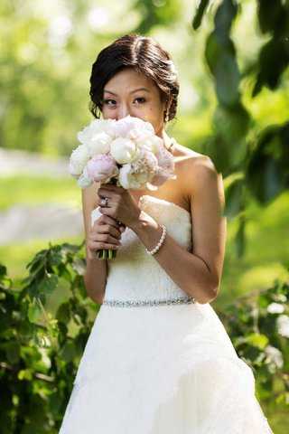 bride-in-a-strapless-monique-lhuillier-gown-holds-a-bouquet-of-pink-and-white-peonies