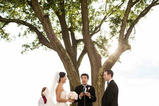 bride-in-a-strapless-monique-lhuillier-gown-and-groom-in-a-black-tuxedo-listen-to-buddhist-hymns