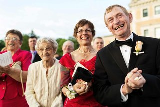 grooms-father-dressed-in-a-black-tuxedo-and-mother-in-a-red-dress