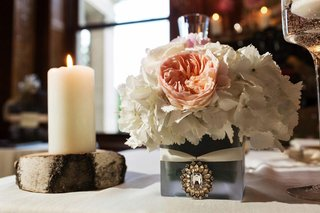 wedding-reception-table-with-small-centerpiece-of-white-flowers-with-a-peach-bloom-in-a-frosted-vase
