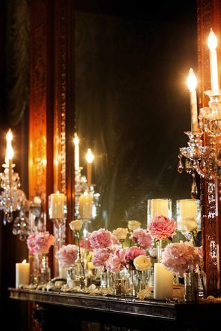 pink-and-white-flowers-and-candles-line-the-ledge-in-front-of-a-mirror-at-wedding-reception