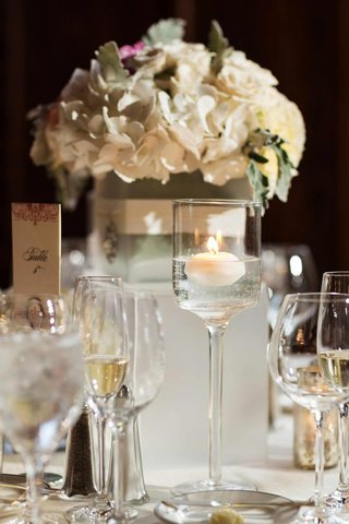 wedding-reception-table-with-white-flowers-and-a-floating-candle-in-a-glass-candle-holder
