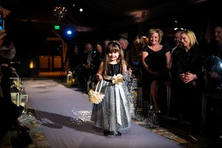 cute-flower-girl-walking-down-aisle-in-black-and-gray-dress-sash-white-basket-throwing-confetti