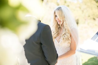 bride-with-veil-galia-lahav-wedding-dress-long-blonde-hair-curls-looking-at-groom-during-ceremony