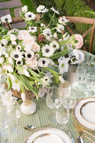 lush-floral-arrangement-with-white-pink-and-green-on-green-table-linens-with-white-and-gold-chargers