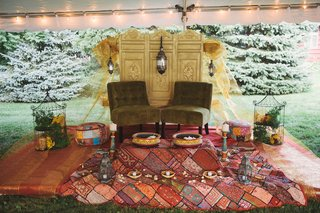 plush-seating-and-mendhi-ceremony-items-on-colorful-linens