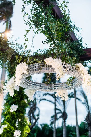 wedding-ceremony-arbor-with-round-crystal-chandelier-decorated-with-white-flowers-greenery