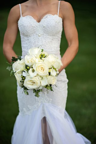 bride-in-a-berta-bridal-gown-holds-bouquet-of-white-roses-and-calla-lilies-greenery