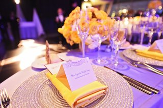 wedding-reception-place-setting-with-silver-charger-yellow-napkin-place-card-with-circular-design