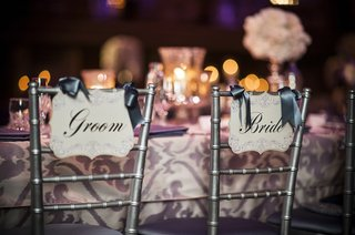 silver-chairs-with-die-cut-bride-and-groom-chair-signs-tied-with-satin-ribbon