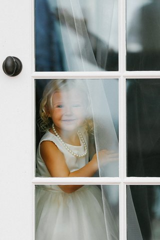 flower-girl-in-white-dress-and-string-of-pearls-looking-out-bridal-suite-window