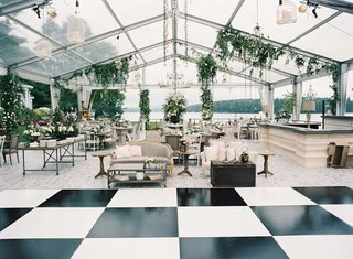 black-and-white-square-checker-dance-floor-clear-tent-wedding-furniture-food-stations-light-bulbs