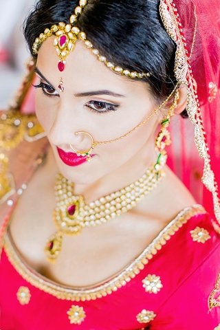 indian-american-bride-with-ruby-and-gold-maang-tikka-emerald-and-gold-nose-ring-with-chain