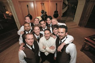 groom-in-white-shirt-and-tie-surrounded-by-groomsmen-with-white-shirts-and-brown-vests