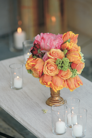 wedding-reception-floral-arrangement-of-orange-pink-green-and-red-flowers-in-a-gold-vase