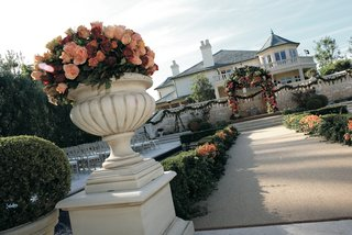 an-urn-full-of-pink-peach-and-red-roses-decorates-the-start-of-a-wedding-aisle