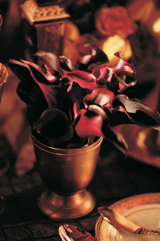 wedding-reception-table-is-decorated-with-red-calla-lilies-in-a-small-golden-vase