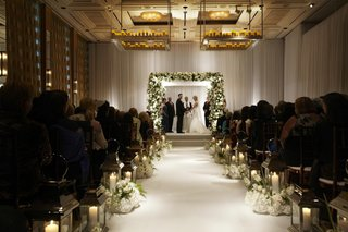 bride-and-groom-beneath-flower-chuppah-in-white-ballroom
