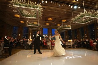 bride-spins-on-wedding-dance-floor-with-plants-hanging-from-ceiling