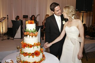bride-and-groom-cut-white-cake-with-orange-flowers