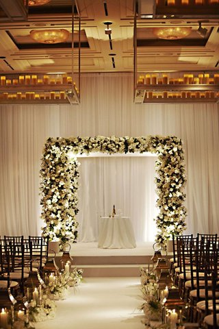 white-flower-and-greenery-chuppah-at-indoor-ceremony